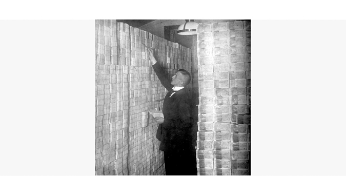Man Between Stacks of Money Demonstrates Hyperinflation